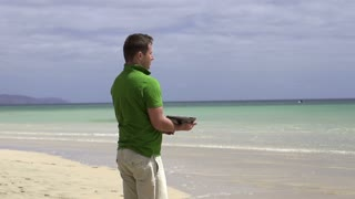 Man with laptop relaxing on the beach, slow motion shot at 240fps
