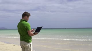 Man with laptop relaxing on the beach, slow motion shot at 60fps