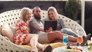 Man with pair of girlfriends using tablet computer while seated in large chair in front of snacks and drinks at lounge and make self picture