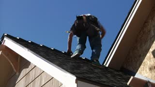 Man With Toolbelt Climbs Down Roof