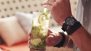 Man with watch and black leather bracelets sips an herbed drink from a tall glass