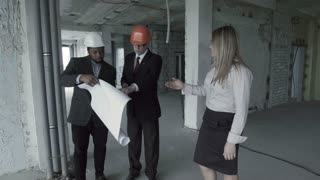 Man, woman, african american in suit and hard hat consider blueprint inside construction site with colleague. Chief engineer architect with designer show plan to customer, discuss, communicate and