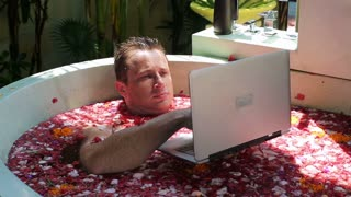 Man working on laptop and relaxing in the spa