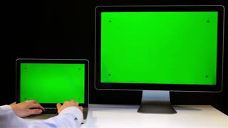 Man Working on the Laptop and Display with a Green Screen at the Workplace.