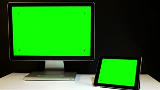 Man Working on the Tablet PC and Display with a Green Screen at the Workplace.