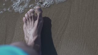 Mans foot walking on the beach, high eagle, slow motion shot at 240fps
