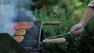 man's hands prepring food on grill