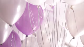 Many white, pink and silver helium balloons floating in the room