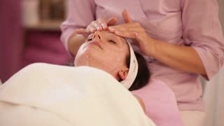 Massage therapist doing professional facial massage to woman at beauty salon. Panning camera