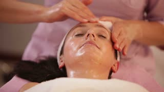 Massage therapist massaging woman's face at beauty spa