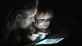 Mather and daughter enjoying a movie on tablet