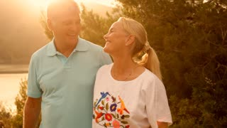 Mature couple walking in countryside in sunset