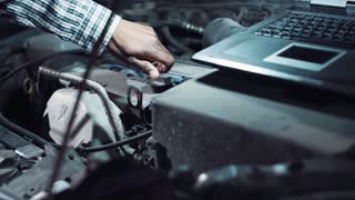 Mechanic doing a diagnostic on a car engine with a portable computer as he performs a routine service or repair after breakdown