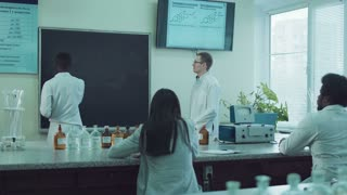 Medical students or pharmacy lab workers in white coats. African American man writing over chalkboard while lector is standing aside. Other people sitting and listening