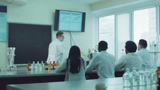 Medical students or pharmacy lab workers in white coats. lector talking about chemistry formula