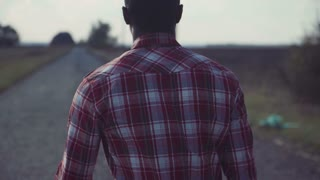Medium shot of back of black man in plaid shirt and blue jeans walks down lonely country road