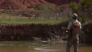 Medium Shot Of Fly Fisherman In Stream With Red Rock Cliffs