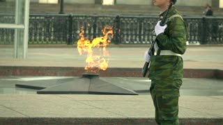 Memorial fire and armed guard in camouflage uniform. Super slow motion long shot