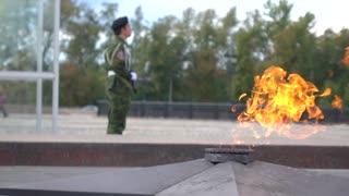 Memorial fire and armed guard wearing camouflage. Super slow motion long shot