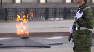 Memorial fire and armed soldier. Super slow motion long shot