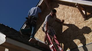 Men Climb Down Ladder On House Construction