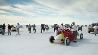 Men Push Streamlined Racecar On Bonneville Salt Flats