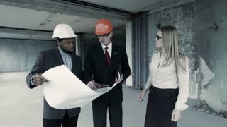 Men, woman in suit and helmet discuss blueprint, communicate with buyer. Chief engineer builder, designer, describe blueprint to african american, show plan to partner or colleague indoor unfinished