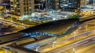 Metro station near Buildings of Jumeirah Lakes Towers with traffic on the road night timelapse. Top view from dubai marina skyscraper