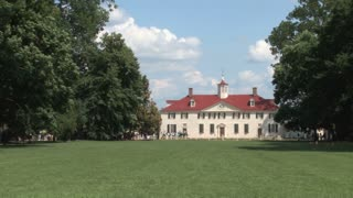 Mid-long shot, main house of Mt. Vernon across lush, tree-lined lawn