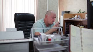 Middle-aged businessman smoking and working in the office