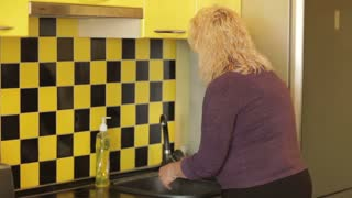 Middle-aged woman washing a plate in the yellow kitchen.