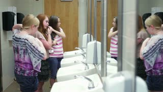 Middle School Girls Chatting In Restroom