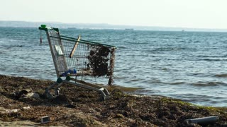 Middle shot of abandoned metal shopping trolley on the beach standing at the edge of the water in evening light