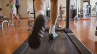 Middle shot of male feet walking on the treadmill in the fitness center