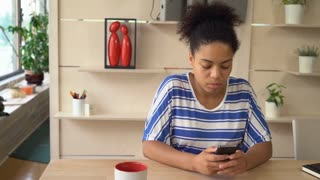 Mixed race african female using app on smartphone. Student chatting in social networking with friend. Multicultural girl sitting at the table in library or waiting room or lounge in campus. Beautiful