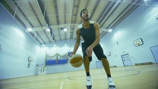 Mixed race basketball player dribbling the ball on the court