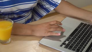Mixed race hands female typing on the laptop. Modern device and glass with orange juice on the wooden table. Girls fingers with natural manicure on the keyboard