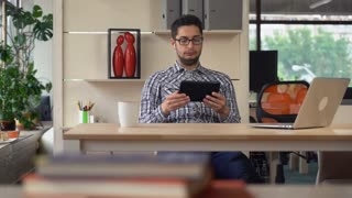 Mixed race man with black hair and glasses call his partner talking via internet. Sitting at the working place at the creative office with wooden table. Male using earphones for speaking with friends