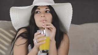 modern brunette woman drinking orange juice in luxury apartment