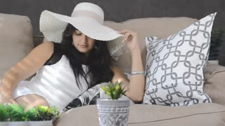 modern brunette woman with hat posing for camera in lifestyle home