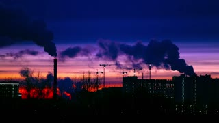 Modern city in the evening at sunset. Smoke comes out of the pipes of power plants and factories of the modern neighborhood on the outskirts of the metropolis. Urbanization.