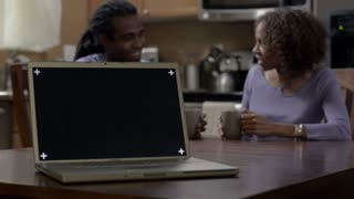 Laughing African American couple in kitchen. Laptop facing camera. Replace screen with ad or message.