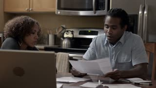 African American husband and wife looking at bills to pay