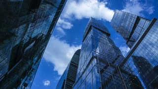 Modern reflective skyscrapers against cloudy sky 4K time lapse. View from below