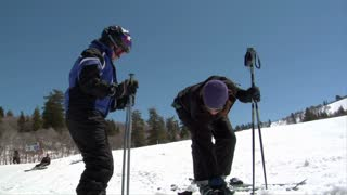 Mom Helping Daughter Into Skis