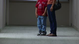 Mom Standing With Son In Hallway