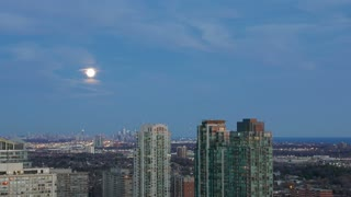 Moonrise Nightfall City Timelapse. The Moon rising at dusk over a city, day to night time lapse.