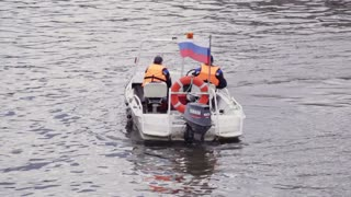 MOSCOW - JUNE 12: Motor-boat of the Russian Emergency Situations Ministry with two men on the Moscow river on the day of opposition protest on Bolotnaya square on June 12, 2013 in Moscow, Russia.