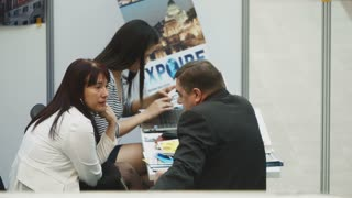 MOSCOW, RUSSIA - APRIL 11, 2014: Man and woman talking on business in one of the agencies at the property exhibition DOMEXPO at Gostiny Dvor