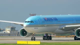 MOSCOW, RUSSIA - JULY 01, 2015: Panning shot of passenger plane of Korean Air airline moving on take-off runway and passing by fire truck at Sheremetyevo Airport